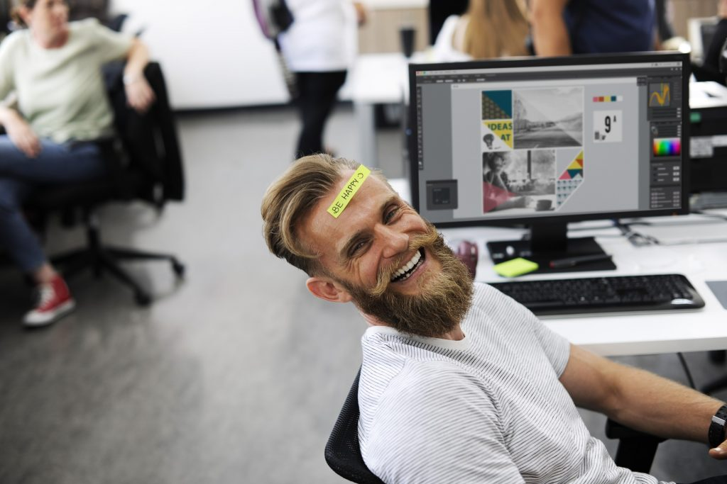 man in front of computer; company culture; be happy